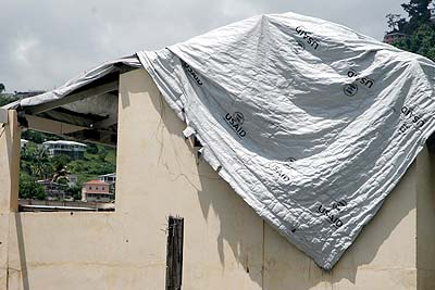 A building's roof patched up with a US Aid tarp .